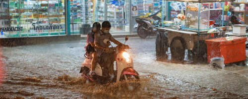 a moped with 2 passengers drives through the water