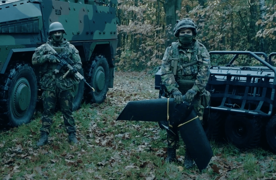 2 soldiers in battle dress and a drone